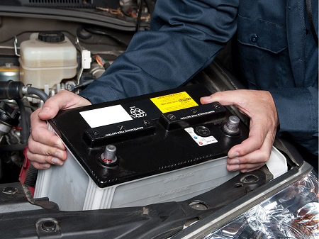 Image That Shows A Car Mechanic Replaces the Battery.