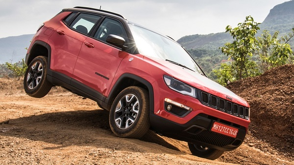 Metallic Red Jeep Compass 4x4 Trail Hawk Compact Crossover SUV On A Rock Surface.
